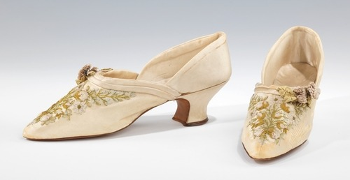 Slippers | c. 1895 - 1905 This pair of dainty slippers features skillfully wrought and subtly hued pastel ribbonwork embroidery, nicely complimented by three-dimensional flowers at the throat. A flirtatious note is added by the curvaceous Louis heel and the flesh-baring d'Orsay cut, which was originally popularized as a men's style by French amateur artist and dandy Alfred Guillaume Gabriel, Count d'Orsay (1801–1852). The Met