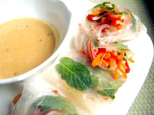 hellyeahrecipes:  Vegetable and Mint Summer Rolls with Spicy Peanut Sauce makes 8 rolls For the sauce: 2 tablespoons creamy organic or natural peanut butter  2 tablespoons rice vinegar  2 teaspoons soy sauce  2 teaspoons sugar  1/2 teaspoon of red pepper flakes For the rolls: 1 1/2 oz cellophane noodles (also called bean threads)  1/2 teaspoon sesame oil  red pepper flakes  1/3 of a seedless cucumber  1/2 of a medium carrot, peeled  1/2 of a red bell pepper  5 baby radishes or 2-3 medium radishes  1 scallion, chopped  1/2 tablespoon rice vinegar  1/2 teaspoon sugar  juice from 1/2 lime  2 tablespoons cilantro leaves  16-24 fresh mint leaves  8 rice paper wrappers Whisk together the ingredients for the sauce and set aside.  Cook the cellophane noodles according to the package directions. We heated a medium sauce pan full of water until almost boiling, then turned off the heat, added the noodles, and let them sit for about 10 minutes. Our noodles came in a 3 3/4 ounce package, and we cooked a bit less than half.  Drain the noodles, put them in a bowl, and toss with the sesame oil and a dash of red pepper flakes.  Use a mandoline to slice the cucumber and carrot into thin strips — or simply julienne by hand. We cut the red pepper by hand, as it was an awkward shape for the mandoline. If you are using large radishes, you can slice them on the mandoline, but we sliced our baby radishes into thin rounds by hand.  Whisk together the rice vinegar, sugar, and lime juice in a large bowl. Add the vegetables and the scallion, and toss to coat.  Fill a round cake pan halfway with hot water. For each wrapper, immerse it in the hot water bath until it softens, which takes about 30 seconds. Lay it on your work surface and fill it first with about 1-2 tablespoons of noodles (you want to have enough for 8 rolls). Then, add 1/8 of the veggie mixture. Add a few sprigs of cilantro and 2-3 mint leaves, depending on how large they are.  To roll up your roll, first fold the edge of the wrapper farthest from you over the filling, then fold in the edges towards the center and continue rolling the filled wrapper towards you until it's closed and snug. If you want to be especially decorative, place the mint leaves closer to the front edge of the wrapper, so that they are rolled into the last layer and show through the top of the finished roll. Continue this process with each of the wrappers.  You may need to change your hot water halfway through. As you finish each roll, place it on a cookie sheet and cover the rolls with a damp towel.  To serve, slice in half with a sharp knife and serve the peanut sauce on the side.