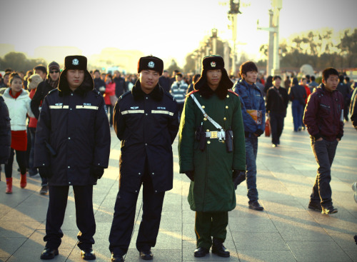 "men in uniform. Two Chinese policemen and one guard or soldier are standing outside the Forbidden city in Beijing. There were so many men in different uniforms there so I am not really sure what their rank or position were. Heaps of tourists were swarming around here to take photos though. What I learned before I got there and that I hope none of you ever do/did is to say yes to the offer (scam) of following locals to a ""Chinese traditional tea ceremony"" since you will have to pay the bill of 700 USD for some tea."