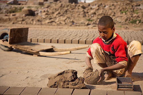 """This young Pakistani boy works in a brick kiln on the outskirts of Lahore in Pakistan, making bricks. His parents owe the brick kiln owner 5,000 Pakistani rupees - less than US $100. Because of this debt, his family works as bonded laborers, which is illegal but all-to-common among brick kiln workers. He does not have the opportunity to attend school, and barring outside intervention, he will likely remain completely illiterate for the rest of his life, as are his parents. "" This is what Conservatives want to turn our country into as well.  They not only don't want foreign aid to be used to rescue people like this, they want workers in our society to be subject to the same ""market forces"" that let things like this happen. Newfilosofee decries, ""I want to go find this boy, hug him, pay all his parents dues and apologize to him that the world is so cruel."" Photo by Damon Lynch"