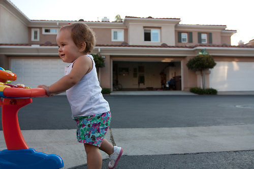 "Ava has been walking the neighborhood trying to get her skills perfected and checking out what the ""big kids"" are doing. If the big kids of the neighborhood are not out on their bikes and skateboards Ava is not interested in being outside either. She will only hang if they are out and she walks around telling them she is 1 year old (almost). Isn't she precious!?"