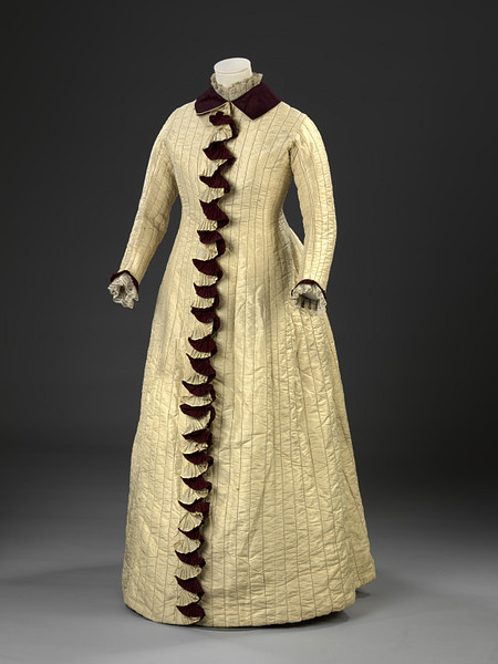 Day Dress | c. 1877   Maroon and yellow pleated folds cascade down the front of this dress concealing the button fastenings. The frills are composed of two narrow lengths of silk which have been knife pleated and then twisted backwards and forwards. This type of trimming was highly fashionable during the 1870s, and pleated flounces also formed elaborate decoration on the front, back, hems and trains of skirts. Creating such regular pleats by hand would have been extremely time-consuming, and contemporary fashion magazines are full of advertisements for 'Kilting Machines', otherwise known as pleating machines. Manufacturers promised that these machines could kilt (knife-pleat) any fabric by steam from the lightest silk to the heaviest serge, with excellent and long-lasting results.