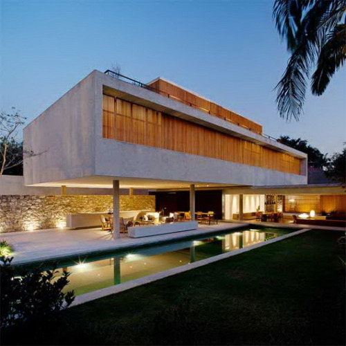 modern house 6by brazilian architect marcio kogansao paulo, brazilthis modern concrete house is organized in 2 transversal volumes and an annex in the back that holds a home office. the lower volume houses the utilities, the kitchen and the living room with door-frames that can be recessed into the walls, and thereby entirely opening the internal space to either side. the upper volume has the private area of the house with the bedrooms and, on the third floor there is a small multiple-use living room alongside an upper deck.