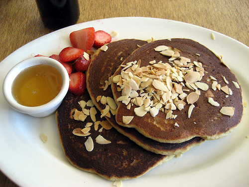 Vegan Pancakes with a side of maple syrup, fresh strawberries and topped with almond flakes. Breakfast of Champions! (via toliveandeatinla.com)
