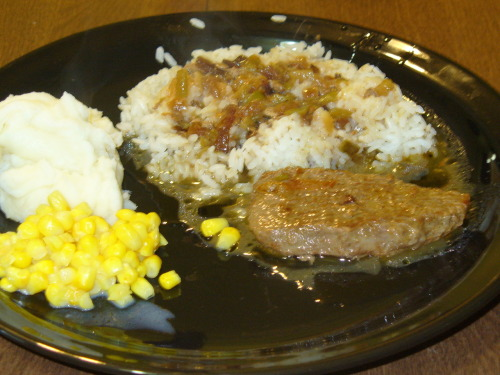 "Steak, Rice, & Gravy One of my favorite meals of all time is steak with rice and gravy. I grew up on it. We ate it a few times each week. It's not only my family, either. In many homes of families across the south, this is a popular dinner menu item. All of my friends, my aunts and uncles, and my grandmother. Before my grandmother died, she was living with my Nannie (my aunt, who was my godmother. In the south, we call our godmothers ""Nannie.""). My Nannie and her family needed to travel out of town for a week, so my husband and I volunteered to take care of my grandmother. On one of the nights, I cooked pork steaks with rice and gravy. I remember eating this meal at her house many times, when I was younger. Instead of sitting and resting as I prepared the meal, she stood next to the stove with her walker, telling me everything she didn't like about my way of cooking her signature dish. Even though I was probably preparing the meal the same way (or very close) that she would have made it, it didn't matter. We eventually had to make her go and sit down. She was much too weak to be standing for so long. The food was delicious, and she still approved of it. The recipe that I'm going to share isn't strictly hers. It's the way I make it. My personal recipe is a mixture of all of the recipes of many people I know. I've taken a little from each one, and that is how I came up with my own. Also, like many recipes from the south, there are no exact measurements to follow. You have to ""eyeball it."" Hope you enjoy it! —- Cooking oil, steak, onions and bell peppers, seasoning, gravy flour, water, cooked rice. Coat the bottom of the pot with the cooking oil of your choice. Heat with medium fire. Add steak, and season. Brown one side, then flip. Add some of the onions and bell peppers that you will be using. Finish browning that side, then add the rest of the onions and bell peppers. Cook a little longer. Add more seasoning to the pot. When the steak is browned, remove the steak from the pot. Raise the fire a little. Stir the onions and bell peppers, browning them a bit. Be sure to scrape any browning marks from the bottom of the pot, it will help your gravy. 1Add some water. Stir. Then add gravy flour. Stir, then continue to add water and gravy flour until the gravy is the consistency you like. Lower the fire and put the meat back into the pot. Add a little more seasoning, and put the lid on the pot. Let simmer until meat is tender. Serve over cooked rice. Mashed potatoes is always a great side dish to compliment this meal."