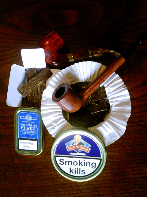 thedailypuffer: Peterson University Flake and Mick McQuaid (Square Cut) pipe tobaccos, both very interesting flakes built to last. Over the McQuaid tin, a surprisingly large Ardor Marte pipe; above lies the exquisite Butz Choquin Montagnarde. ( The picture was taken in the Christmas of 2009, hence the large bowls built for generous smokes. )  Man this guy is fantastic. Great pictures, great pipes, great info. Top notch blogger.