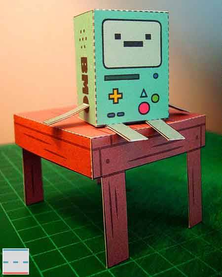 "Papercraft for Beemo, that adorable and portable video game console you'll often see pop up in Adventure Time. It can walk around! It can even talk! And it also plays funky titles like Adventure Masters (with Bit.Trip-esque graphics and dueling Abraham Lincolns) and Bug Battle. Did you see last Monday's new half-episode, in which Donny (the jerk) breaks one of Beemo's controllers? Man, I was pissed. Let's see how long this clip stays up:     In the video, you'll hear that Beemo has a Korean female's voice (likely the same voice actress as Lady Rainicorn); knowing it's a Korean handheld somehow makes the made-up console even more interesting! I wonder if she's related to Tiny at all? He's mentioned to us before that he'd love to visit Korea one day… Oh yeah, you can download a template for the Beemo papercraft designed by Bryan Green at this link. See also: Beemo's Tiny Cartridge debut, Super Mario Bros. 2-style Adventure Time spritesheet [Via Paperkraft, this soon-to-be-taken-down video for Adventure Time's ""Donny"" episode]"