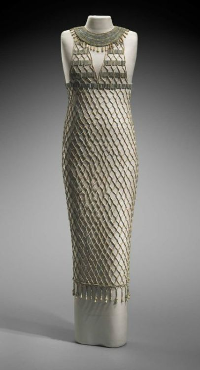Beadnet dress | Egyptian Old Kingdom, Dynasty 4, reign of Khufu |2551–2528 B.C. Depictions of women in Egyptian art occasionally feature garments decorated with an overall lozenge pattern. This design is believed to represent beadwork, which was either sewn onto a linen dress or worked into a separate net worn over the linen. This beadnet dress is the earliest surviving example of such a garment. It has been painstakingly reassembled from approximately seven thousand beads found in an undisturbed burial of a female contemporary of King Khufu. Although their string had disintegrated, a few beads still lay in their original pattern on and around the mummy, permitting an accurate reconstruction. The color of the beads has faded, but the beadnet was originally blue and blue green in imitation of lapis lazuli and turquoise. (Boston MFA)