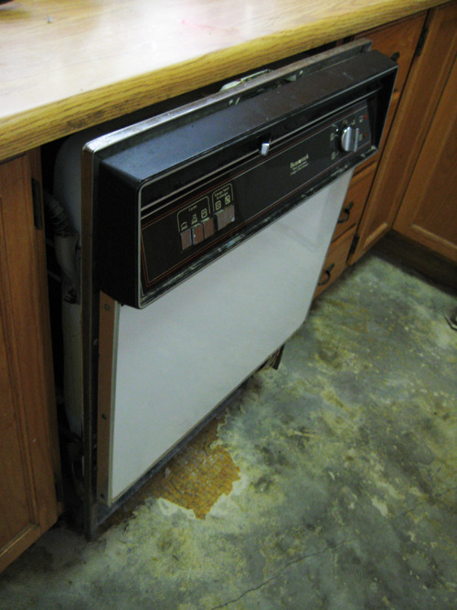 "This is a photo of my non-functioning dishwasher, but that's not why I posted it. It is surrounded by my (real) wood cabinetry (awaiting painting… someday), and my (fake) wood countertop (kitschy, yes, but in such good condition that it comes 'round full circle to clever), but that's also not why I posted it. No, I posted this because it's the only readily accessible photo in which you can see the current state of my kitchen floor. There are many more, but I'm lazy and pissed off today, so you'll have to make do with this. After two months of hoping it would just magically refinish itself, I've finally bit the bullet today and tried tackling it again. The floor was once covered with two flimsy layers of rolled linoleum, the oldest dating back to 1985. Removing the lino was easy, although it left behind the paper backing in some areas, which was less pleasant. That's when I discovered razor scrapers, which, when combined with hot water, easily remove the paper backing. What I was not prepared for? Dry, hardened yellow mastic. This is the glue that's used to hold the linoleum to the raw cement floor. As you can see from the photo, while some it has been lifted (grey areas), vast sections of yellowed, ugly cement remain. The yellow areas are the spots where the glue has been poured on so thickly that it has filled every pit and scratch in the cement, making removing it a huge chore. Also in the photo, you'll notice the long crack that nearly bisects the entire floor… but more about that in a minute. Let's talk about mastic, and glue removal in general. Here's a fun fact: there is no guarantee that a chemical preparation of your choice will remove the glue in question, since just as each ""glue gone"" bottle boasts a mixture of different ingredients, so do the various glue formulations. I am not fond of strong chemicals, and I don't have the luxury of a fat bank account, so experimentation with pricy glue removal potions isn't really an option. Ultimately, all my research has culminated into one inescapable concept: ""mechanical"". Mechanical removal of the mastic is the only way guaranteed to work. Currently, I am using hot water, a wire brush, and the aforementioned razor scraper for detail work. Here's the process: boil water; ladle boiling water onto small area; scrub now wet area with wire brush; repeat… endlessly. It takes forever. I am not interested in renting a floor sander. My understanding is that they can get too overzealous with the sanding and leave unevenness and grind marks. I am contemplating picking up a cheap grinder and wire brush attachment and at least taking a little of the elbow grease out of it, but until then, it's manual, mechanical removal for me. Now, about the crack. It kinda doesn't bother me. I'm sure people that know me well might read this and be surprised, but it doesn't. I have some leftover dark grey grout from something else, so I'll likely fill it with that, but I won't be heartbroken if it doesn't match… I'll just call it veining and leave it at that. If any of you out there have any experience with mastic or glue removal, and have any suggestions, I'd be happy to hear them… you know where I'll be, on my knees on the kitchen floor!"