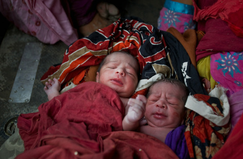 Newborn twin boys lay covered up in a blanket on the floor of a Pakistani Army helicopter, as mother Zada Perveen (unseen) rests after being rescued by Pakistan Army soldiers during air rescue operations on August 9, 2010 over the village of Sanawan in the Muzaffargarh district of Pakistan. Of the twin boys, un-named at the time, the first was born 15 minutes before mid day and the other twin was born as the Army rescue helicopter was circling above to find a safe landing position on a road surrounded by flood waters. The mother was then carried on a makeshift bed through chest deep flood waters to the awaiting Pakistan Army helicopter. (Daniel Berehulak/Getty Images)