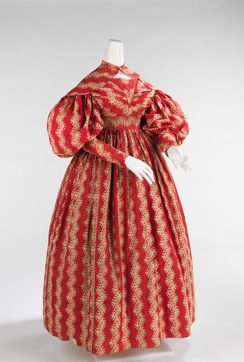 Day Dress | c. 1835 This transitional style indicates the aesthetic of its period. The large gigot sleeves were popular from the early 1830s through 1836 when they began to diminish to the tightly fitted sleeves of the following period. This type of sleeve was generally supported by whalebone or down filling. Another indication of its transitional disposition is the waist height and the full bell-shaped skirts. The rich color and lively pattern is engaging and in line with the mode of the day.  (Met Museum)