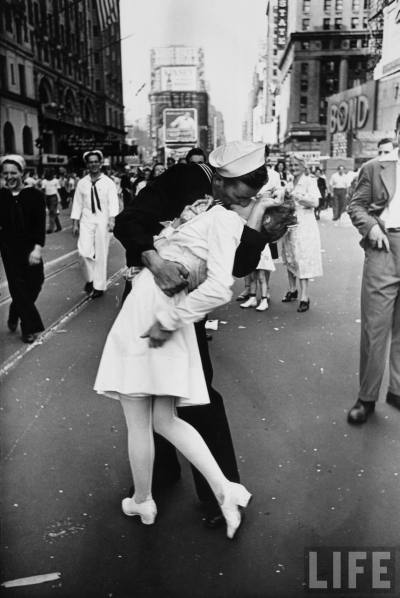 "V–J day in Times Square, a photograph by Alfred Eisenstaedt, was published in Life in 1945 with the caption, ""In  New York's Times Square a white-clad girl clutches her purse and skirt  as an uninhibited sailor plants his lips squarely on hers""."