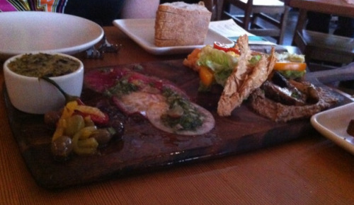 "That's the vegan charcuterie plate from Gather in Berkeley. First off, it's pronounced, ""shar-cooter-ee"". (Tee hee). Unlike in my piggy dreams, it's not a giant plate of vegan sausages topped with more vegan sausages (never-ending vegan sausages!) but rather, a refined spread of the freshest market vegetables. Healthy? Boo! Actually, no, I can roll with the snobbiest eco-foodies around. Bring on your fancy vegetables, Gather. Bring me your roulades and your chiffonades and your other bougie food words I don't fully understand. The charcuterie (tee) is a delightful dish of different vegetables sliced, diced, julienned, and combined to create a taste sensation heretofore unknown. Mushroom pâté, eggplant ""brandade,"" and carpaccio of watermelon radish and turnip. Don't understand a word I just typed but damn, was it tasty. They also have amaaaaazing cocktails that include infused vodkas and fresh muddled fruit and unique liquors. They are also a million dollars each but you only live (your drunken life) once! I also recommend the vegan soup, it is fantastic. All in all, lots of good vegan options in a very Berkeley environment WHICH I LOVE BECAUSE I LOVE EVERYTHING ABOUT ALL CITIES. I don't know, I'm tired and I think you should all check out the vegan charcuterie (teehee) plate when you get a few extra dimes in your pocket. Plus, if you're still hungry, you can head next door to Saturn and get your french fry on. That's right I said GET YOUR FRENCH FRY ON. Learn it, live it, love it. OH AND I FORGOT TO MENTION (thanks, MD!), the vegan pizza with lipstick peppers and cashew cheese was the bomb GET IT. A good chunk of this review was straight gaffled from my SFist column, which is all about the best of the best of vegan eats in and around San Francisco. If you go ""like"" it and perhaps leave a complimentary comment and then shoot me an email, I'll send you a complimentary comment over email that I tailor to your specific awesomeness. I can also send you an insult if you're into that, you big weirdo."