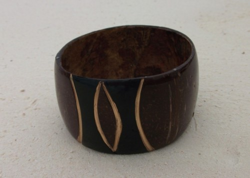 This beautifully handcrafted bangle is made of coconut shell, and was sourced from the outskirts of the Tanzanian city, Dar Es Salaam.Its stunning, one off design is highlighed with accents of gold, and varnished in order to set off the rich colours.Only one available