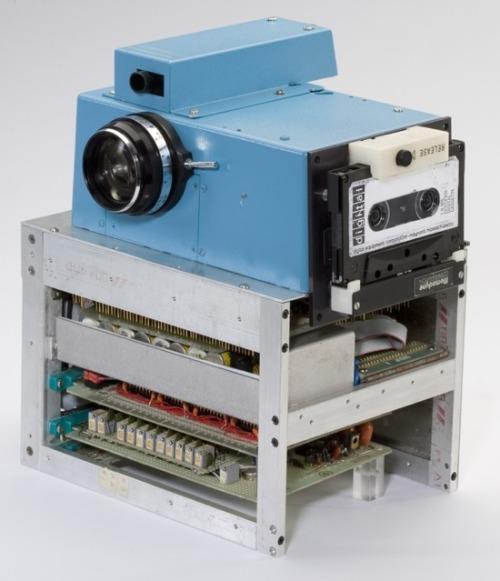 "nerdology:  Above is the first digital camera.  It was made by Steve Sasson working for Kodak in 1975. 1975! Using ""a lens from a Super 8 camera, a whole stack of ni-cad batteries, a digital to analog converter from a voltmeter, [and] a highly experimental CCD.""  Oh and that cassette tape on the side, thats are how the pictures are stored.  The camera captured a 100-line image onto that cassette-tape, yet even that tiny picture took a mind-numbing 23 seconds to write. Playback was possibly clunkier still, using another tape-player hooked up to a frame-storing devices that interpolated those 100 lines to an NTSC-compatible 400-line image and then showed it on a regular TV-screen.  Though it was built in 1975 and patented in 1978 it stayed hidden from the public until 2001.  It still remains in Steve Sasson's possession still. [Wired]"