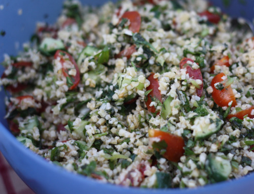 Tabbouleh / Tab(b)ouli Salad Among the many treasures of my new neighborhood in Northeast Minneapolis is the tabbouleh from Emily's Lebanese Deli (not to be confused with a lesbian deli). A traditional Lebanese dish, tabbouleh is a salad made with bulgur wheat (warning: not gluten free), a LOT of parsley, mint, tomato, lemon, green onions, olive oil, and salt. Emily's version plays up the lemon quite a bit and is a light but punchy accompaniment to any of the other meatier main dishes. Or it could stand as the star with some pita or rice.  I have made tabbouleh a few times at home, and it is a great recipe in the summer time. Light, easy to transport to picnics, and makes use of a lot of items that are in-season at the farmer's market. Like many other salads, the beauty lies in its abundant returns with respect to flavor and satisfaction, especially given the ease of execution. If you are trying to watch your gluten intake, you can substitute quinoa or brown rice, prepared according to the proper water:grain ratio. Tabbouleh, from the Barefoot Contessa Parties! cookbook (serves 8) 1 c. bulgar wheat (or quinoa) 1-1/2 c. boiling water (2:1 ratio of water:quinoa, if you're subbing) 1/4 c. freshly squeezed lemon juice (about 2 lemons) 1/4 c. olive oil  3-1/2 tsp. kosher salt 1 c. minced green onions/scallions, white and green parts  1 c. chopped fresh mint leaves 1 c. chopped flat-leaf parsley 1 hothouse cucumber, unpeeled, seeded, and medium diced 2 c. cherry tomatoes, cut in half 1 tsp. freshly ground black pepper Place the bulgar in a large bowl, pour in boiling water, add lemon juice, olive oil, and 1-1/2 tsp. salt. Stir, then allow to stand at room temperature for about an hour. Add the green onions, mint, parsley, cucumber, tomatoes, 2 tsp. salt and the pepper. Mix well. Season to taste and serve, or cover and refrigerate. It really tastes best after a few hours in the fridge.