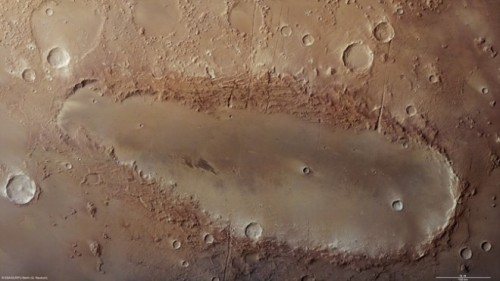 "Weird Oblong Crater Deepens Mars Mystery This amoeba-shaped depression on Mars, called Orcus Patera, has had planetary scientists scratching their heads for decades. Despite this sharp new image from the European Space Agency's Mars Express spacecraft, the crater's origin is a complete mystery.Orcus Patera, discovered in 1965 by the Mariner 4 spacecraft, is located near Mars' equator, between the volcanoes Elysium Mons and Olympus Mons. At 236 miles long, it would stretch from New York to Boston on Earth. Its rim rises over a mile above the surrounding plains, and its floor lies 1,300 to 1,900 feet below its surroundings.But in spite of lying between two volcanoes and its designation as a patera — the name for deep, complex or irregularly shaped volcanic craters — scientists aren't at all sure that Orcus Patera has a volcanic origin story. It could be a large impact crater that was originally round but later deformed by compressional forces. Or it could have formed after the erosion of aligned impact craters. The most likely explanation is that it was made in an oblique impact, when a small body struck the surface at a very shallow angle, like a rock skipping on a pond.The new images show that the crater's rim is criss-crossed by rift-valley-like structures called graben, which are evidence for active tectonic forces in the area. Smaller graben are also visible inside the depression itself, suggesting that several tectonic events have stretched the ground. The depression also shows ""wrinkle edges,"" which indicate that the ground has been compressed as well as stretched. The dark shapes near the center of the depression were probably formed when dark material dug up by small impacts in the depression was blown around by the wind.But these features all appeared after Orcus Patera was formed. The oblong crater's origin is still a mystery.___Story: Wired Science"