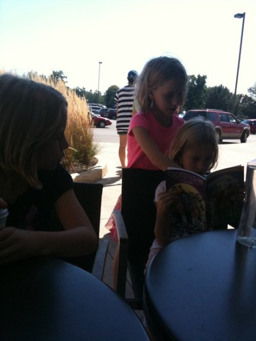 "My triplets reading ""Archie's Haunted House"" at a coffee shop in Indianapolis"