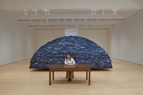 "hyperallergic:  Ann Hamilton, indigo blue From SF MOMA: Indigo blue is comprised of some 18,000 pieces of used, blue work clothes that are folded and piled on a steel-and-wood platform. In front of the platform are a wooden table and stool where an attendant sits and erases text from a book titled International Law Situations, published by the Naval War College, exemplifying Hamilton's incorporation of an active, physical presence within her work. The attendant moistens an eraser with saliva, rubs out lines of text, and allows the eraser filings to accumulate into a pile at the book's edge. Hamilton has described this activity as a way of ""using the body to re-mark history—taking the mechanically reproduced text and replacing it with the mark of the body."" The work also acts as a surrogate voice for the anonymous laborers represented by the mountain of blue uniforms located behind the work table."