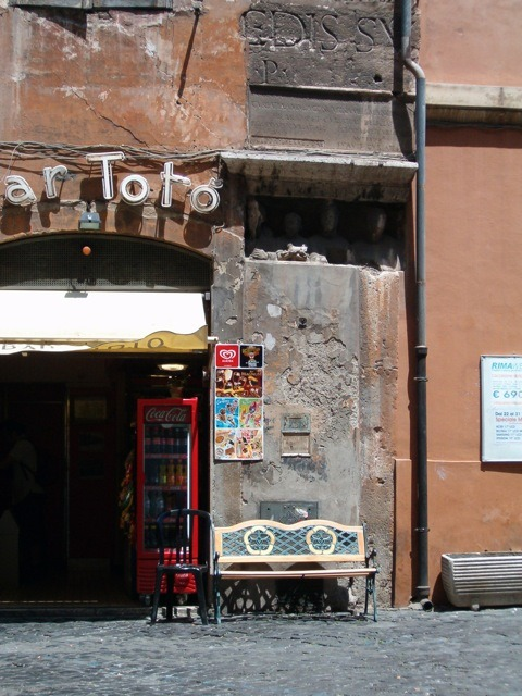 Coffee bar in Rome with two-millennia-old stuff stuck in the wall (the lumpy things in the shadow are portraits of a family from their tomb, and there are two bits of ancient Roman inscriptions above). Summer, 2006.