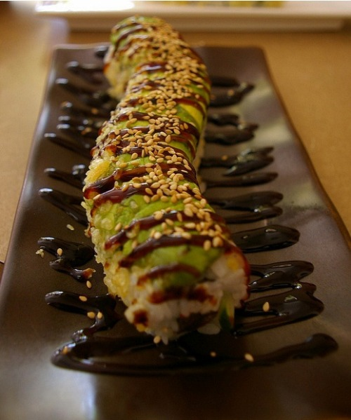 This looks like a delicious Green Dragon roll! The inside usually includes eel and cucumber, whatever other ingredients are added depend on the restaurant! This roll is almost always topped with avocado :3