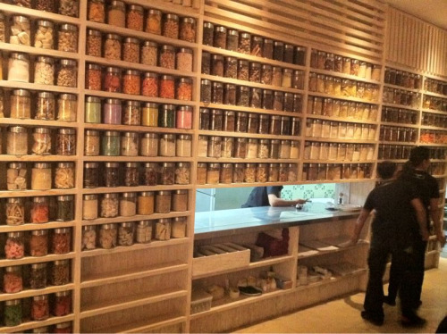 Some of the inside walls were shelves filled with jars of different colored and shaped items, from pasta to seedpods to rubber toys! This is the servery wall from the kitchen. The photo quality is low due to the lack of light.