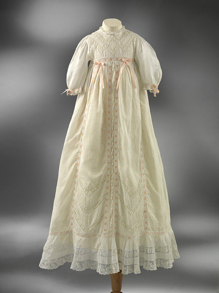 Christening Gown | c. 1900-20 Over the years this Christening gown has gained the nickname of 'The Bin Dress' because an observant member of the donor's family pulled it out of a dustbin in the early 1930s and rescued it for further use. It is unlikely that the Museum will ever know the true story of its presence in the bin: perhaps a dispute or even a tragedy, or maybe by then it was simply too old-fashioned? Its lace decoration is in a style that was particularly fashionable around 1900, but by the 1930s, when the dress was thrown away, the latest Christening robes were often much shorter than this and made of synthetic fabrics that were easier to iron.