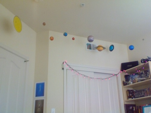 This is my puzzle-model Solar System. I said I would post a picture when I have it up. Ta-da. I'll probably take a better picture sometime later. But you get the idea! It's ridiculously awesome. Hooray. The best part is they included Pluto. If you want to buy it~! I also bought solar system wall stickers, which I am returning because the cut of Saturn and Uranus are completely off.