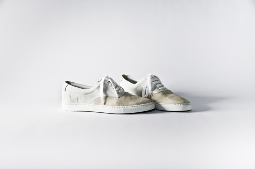 "Shoes by Common Projects. In my mind, Meredith Overton's shoes are much like these. Common Projects shoes are simply, elegantly made out of quality materials; the logo is only printed on the insole; and the only visible branding is a serial number, stamped in gold on the outer heel. From Zero History:  ""She liked your shoes."" ""She really got them. I'm not sure anyone else ever did, to the same extent. She got what I was trying to get away from. The seasons, the bullshit, the stuff that wore out, fell apart, wasn't real. I'd been that girl, walking across Paris, to the next shoot, no money for a Métro card, and I'd imagined those shoes. And when you imagine something like that, you imagine a world. You imagine the world those shoes come from, and you wonder if they could happen here, in this world, the one with all the bullshit. And sometimes they can. For a season or two."""