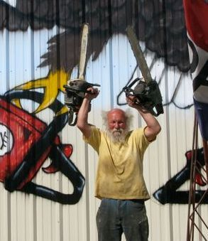 "This is Ray Murphy, a chainsaw artist from coastal Maine, his saws aloft. The guru of ""stunt entertainment  chainsaw art"", his performance includes including  sawing numbers one to 17 on a toothpick and the alphabet on a pencil. We met him."