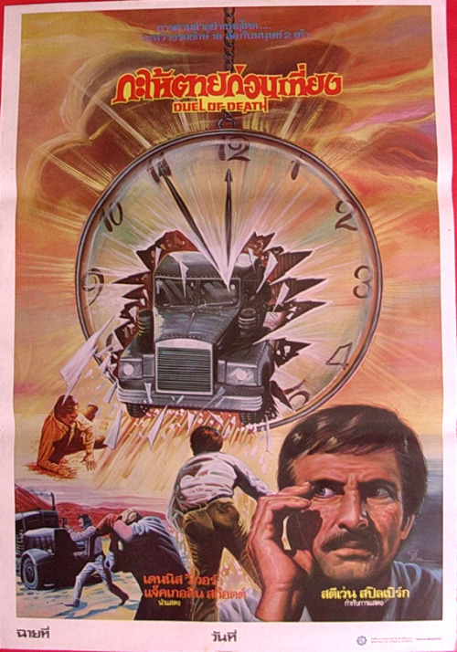 "I'm not sure what this is a poster for. ""Duel of death""?! Is it Le salaire de la peur? The guy, bottom left, appears to be on a mobile phone so that would suggest not. Or is it another mysterious time traveller?  Edit 07/02/11: Turns out it is ""Duel"", Steven Spielberg's first film."