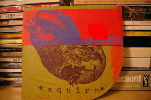 "Band: Squirm*OrchestraAlbum: Somersaults Inside OurselvesPrice: $0.99  You can't judge a book by its cover, but you can be curious enough to buy a CD for about a buck because of the packaging. Vinyl lovers like to turn their nose down on CDs for so many things, least of all the packaging. ""With vinyl, you get this massive, beautiful canvas,"" they say, or something along those lines. But anyone who really wants to get creative with packaging artwork can work with the tools and confines they're given. Vinyl, cassette, CD, 8-track, MiniDisc, MP3, whatever.  I barely know what Somersaults Inside Ourselves sounds like: I listened to it once, and it barely registered. I'm listening to it for a second time as I type, and I know why I haven't returned. Squirm*Orchestra has got some gumption and ideas, but their sound seems to spill out of their cauldron of songs in ways no one wants. Electrionic blips float one way, shades of noise pop in another way and disappear. There's some excellent drumming in there, but it all seems to crash together and not make much sense.  One could say the same for the album artwork. It's surely ambitious, but it seems almost haphazardly scrapped together. Which certainly stands out, and after rows and rows of jewel cases, a ludicrously shaped envelope that's practically threaded together can do wonders to one's curiosity.  Sometimes the kind of off-the-wall displays of creativity like Squirm*Orchestra's Somersaults Inside Ourselves can elicit a range of reactions. Sure, maybe I didn't like the music too much, but the experience of the whole package evoked a certain… well, I still can't make up my mind on that. Just like Squirm*Orchestra, I also appear to be too overwhelmed to decide which way to go with Somersaults Inside Ourselves."