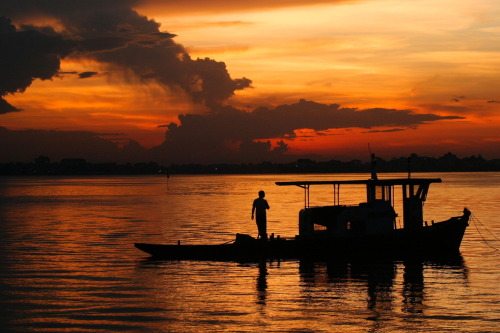 07 July 2003 | A boatman surveys the water as the sun sets on West Lake, Hanoi, Vietnam. Going with a Hanoi theme these days, as the city goes bonkers for its 1000th anniversary on 10/10/10. I think this is the way most Hanoians (at least the older ones) want their city to be viewed - traditional, romantic, peaceful…. Sometimes it is those things, but most usually not. It's frenetic, loud, chaotic, and in its own weird, haphazard, seemingly accidental way, quite modern.