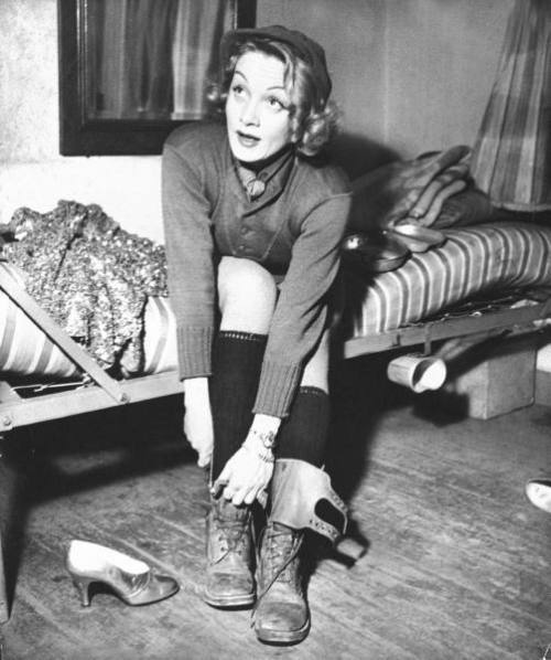 Dietrich in Germany, preparing to don her sequined evening gown & gold pumps to perform onstage during USO show for a US Army, February,1945  by George Silk from LIFE
