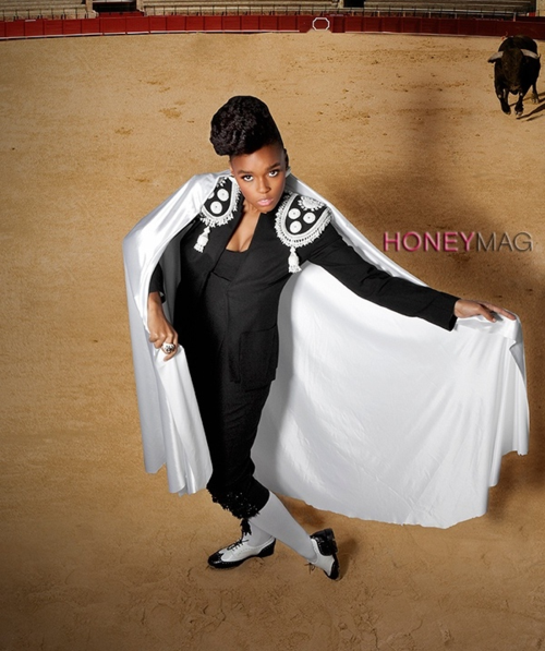 [Description: Janelle Monae, in a black bullfighter's outfit, brandishes a white cape. In the background, a bull appears to be running toward her.]