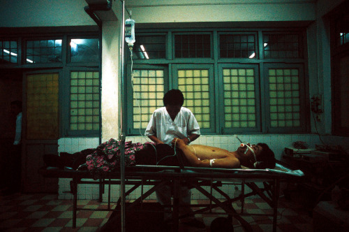 28 October 2002 | A doctor tends to Pham Dang Hieu, who was rushed to the emergency room of Hanoi's Viet Duc University Hospital with severe head trauma after a motorbike accident.  This was one of my very first assignments for TIME Magazine, for a story about the high rate of motorbike accidents, head injuries and road fatalities (at the time, I recall 35 deaths / day in Vietnam). It was also on this assignment that I first met American Greig Craft, who started the Asia Injury Prevention Foundation to address this problem. I'm pretty sure it was largely due to Greig's efforts that the Vietnamese government instituted a mandatory helmet law in December 2007.