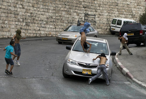 quelowat:  An Israeli motorist runs down a  masked Palestinian youth who was standing among a group of youngsters  throwing stones at Israeli cars on October 8, 2010 in the mostly Arab  east Jerusalem neighborhood of Silwan.  ILIA YEFIMOVICH/AFP/Getty Images  it's pictures like this that make me never want to be a photographer. i could never be a complicit observer of something like this (i mean i don't know what happened after he/she took this photo, whether they helped those kids and so on, but still). all i know is i couldn't focus through a viewfinder in moments like these, i'd smash in that guy's windows and his face.