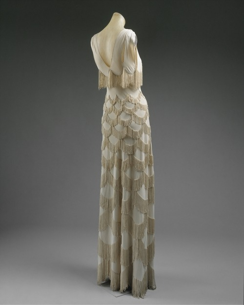 "Evening dress ca. 1938 via The Costume Institute of The Metropolitan Museum of Art ""Though there are separate specialists for applied braid and fringe, known as the crépinières, Vionnet chose in this instance to employ an embroidery of individual graduated lengths of silk thread passed and looped through the fabric, with each thread forming two drops of fringe. The scallop arcs constitute the sole decoration of the dress."""