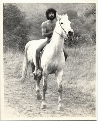 naked hippie man riding a white horse vintage style