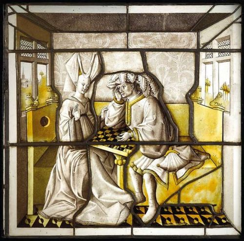 "missfolly:  Stained glass of Chess Players from the Hotel de la Bessée (Villefranche sur Saône) (1430-1440) 'The game of chess as a metaphor for love ritual, permeates the culture of the late Middle Ages in literature as in the figurative arts. One of the most attractive examples of this craze is offered by the stained glass of the fifteenth century.  As one of the oldest stained glass preserved civil, it recreates the lifestyle of a cultured elite. Both players wear stylish clothes and extravagant hats, as was fashionable in the fifteenth century. The lady wears a long robe of cloth lined with fur. She shaved the top of the forehead, as usual elegant women in the early fifteenth century, and wears a horned headdress so-called ""split roll"". His partner is wearing a beautiful chaperone that forms a turban on his head. The gray and yellow - two favorite techniques of painting on glass - are employed on a very pure glass, of varying thickness, sometimes very thin. Its remarkable quality of execution is also one of the best artworks of the Lyons area in the mid-fifteenth century.'"