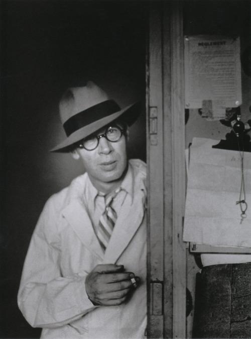 Brassaï Henry Miller au chapeau dans l'embrasure de la porte  [Henry Miller Standing in a Doorway Wearing a Hat] Hôtel des Terrasses, Paris, circa 1931-1932 From Brassaï, Paris