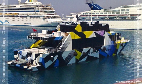 "This is the Guilty, a yacht owned by Dakis Jouannou. The dazzle-style paint scheme was designed by Jeff Koons. Surely Huberus Bigend must want one of these, if he doesn't have one already. Although it's possible that he considers this unambitious or passé, considering he's got an ekranoplan and all. From Zero History:  ""He's curating suits that do retinal damage, these days."" ""He has no taste at all, but he behaves as if he's had it removed, elective surgery. Perhaps he did.""  And:  What Fiona called ""dazzle"", though, was new to him. Fiona said it had been invented by a painter, a Vorticist. He'd Google it, when he had the time."