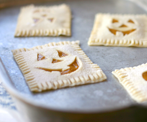 "Pumpkin Poptarts Ingredients: 1 cup pumpkin puree 1/4 cup sugar 1 egg 1 package refrigerated pie crust Glaze: 1 cup powdered sugar 2 tablespoon milk 1 tablespoon light corn syrup 1/2 teaspoon vanilla Directions: In a large bowl, mix together pumpkin puree, sugar, and egg. Unroll pie crust, cut the edges off to make a large square, then cut the pie crust into three equal rectangles (about 2"" x 3""). Spoon a small amount of pumpkin mixture into the center of one of the rectangles, taking care to not let the filling ooze near the edges. Use a small paring knife to carve jack-o-lantern faces into a second rectangle. Gently lay the carved piece over the pumpkin filling, then press the edges firmly together with a fork. Transfer to a cookie sheet and bake in an oven preheated to 400 degrees for 8-10 minutes, or just until the edges of the poptart begin to turn golden brown. In a large bowl, mix together the powdered sugar, milk, corn syrup, and vanilla. Drizzle glaze over hot pumpkin poptarts. Allow to cool on a cooling rack before serving."