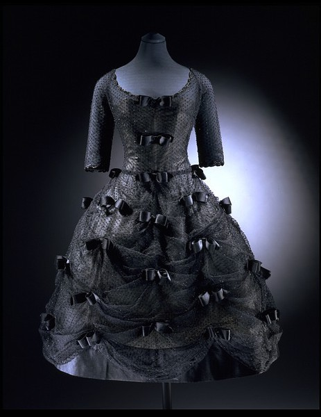 "omgthatdress:  ""Bal Masque"" cocktail dress ca. 1958 via The Victoria & Albert Museum ""The Duchess of Windsor patronised top Paris designers throughout her life. Christian Dior was a particular favourite. She was sixty-two years old when she selected this black evening dress. It was called 'Bal Masque' and came from the 1958 spring-summer collection designed by Yves Saint Laurent for the house of Dior. The style of the dress is influenced by the bell-shaped skirts fashionable in the 1860s. This influence can also been seen in the way it has been constructed. This dress has a tightly fitted boned corset and a bell-shaped skirt supported by a layered petticoat.The lightweight overdress is made of a double layer of spotted black tulle. It is studded with sparkling black bugle beads which are arranged in festoons caught at intervals by 42 bows of satin ribbon. The dress buttons down the back."""