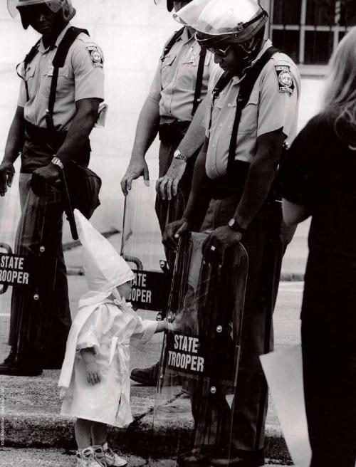 pullofftheband-aid:  bluesey: Here is a Georgia State Trooper in riot gear at a KKK protest in a north Georgia city back in the 80s. The Trooper is black. Standing in front of him and touching his shield is a curious little boy dressed in a Klan hood and robe. I have stared at this picture and wondered what must have been going through that Trooper's mind. Before the Trooper is an innocent child who is being taught to hate him because of the color of his skin. The child doesn't understand what he is being taught, and at this point he doesn't seem to care. Like any other child his curiosity takes hold and he wants to explore this new thing that this man is holding probably because he can see his reflection in it and that's a neat thing and he wants to check it out. In this picture I see innocence mixed with hate, the irony of a black man protecting the right of white people to assemble in protest against him, temperance in the face of ignorance, and hope that racism can be broken because this young boy may remember that a black man smiled at him once and he didn't seem so bad after all.  Wow pretty powerful