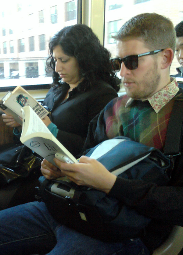 hotguysreadingbooks:  This guy may be the most convincing visual evidence that reading is cool. I love how effortlessly he pulls off wearing a rainbow argyle sweater over a floral shirt. The submitter, Cara, also featured him on her fashion blog after spotting him on the Chicago red line. (thanks, Cara!) — Posted by Kristin