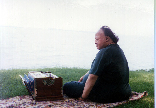 The late legendary singer Nusrat Fateh Ali Khan, relaxes as he sports a black t-shirt, wind-swept hair, and his beloved harmonium.
