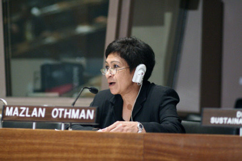 Director of the UN Office for Outer Space Affairs Mazlan Othman wears an earpiece as she taps and listens into secret alien conversations, giving international organizations everywhere a cautious heads up.