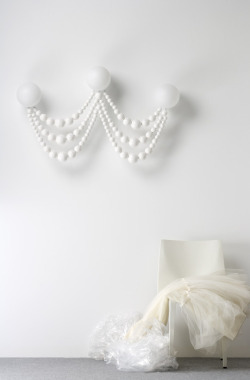 Pearl is a chandelier in shape of an over sized brooch. By Swedish design studio Asshof & Brogård.