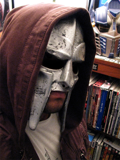 "rocom:  How To Make an MF DOOM Mask for Under $20 I went to the local Party City yesterday and came across a ""Centurion Helmet"" in one of the aisles. I looked at it and did a quick double take saying, ""Whoa! That's the MF DOOM mask!"" Well, almost. It was made of rubber and a full helmet, not just the faceplate like DOOM wears. I purchased it for $15 and modified it to look just like MF DOOM's mask. If you like it, here's how to make your own! You will need: A $15 centurion helmet (sometimes listed as a gladiator helmet online) Scissors Roll of Elastic Stapler (with staples inside) Carefully cut the top and back parts of the helmet off, leaving only the front part of the rubber mask in tact. Look up some photos of MF DOOM on Google image search to know what parts to cut-off and what parts to leave alone. Cut a piece of elastic that will fit snug to your head. Do not cut a piece that is too small or else the mask will fit too tight to your face. Staple each end of the elastic to opposite sides of the mask and you are done! The mouth area of the mask covered too much of my top lip, so I cut off enough to match the actual mask that DOOM wears. If you're an MF DOOM fan and not too worried about owning an actual metal replica, this cheap version looks very close to the actual thing and you can make it just in time for Halloween."